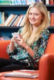 Studente adolescente femminile Using Mobile Phone in biblioteca Fotografie Stock Libere da Diritti