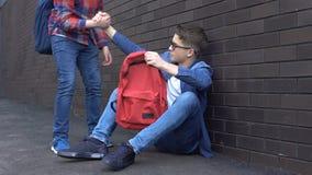 Studente adolescente gentile che dà mano amica al ragazzo oppresso del nerd, amico complementare archivi video