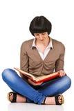 Studente adorabile che si siede su un pavimento e colto il libro, isolato Fotografia Stock Libera da Diritti