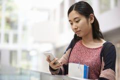 Studente adulto femminile asiatico che utilizza telefono nell'ingresso dell'università Fotografia Stock Libera da Diritti