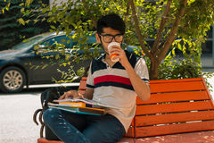 Studente affascinante che si siede su un caffè bevente del banco e che tiene un libro Immagine Stock