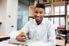 Studente africano bello in biblioteca che chiacchiera dal suo telefono Fotografie Stock