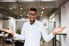 Studente africano felice in biblioteca che gesturing con le mani Fotografie Stock