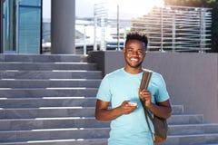 Studente africano sorridente che cammina dalle scale con la borsa e lo Smart Phone Fotografia Stock Libera da Diritti