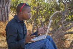 Studente africano sorridente che per mezzo di un computer portatile Fotografia Stock