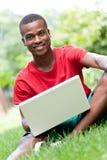 Studente africano sorridente dei giovani che si siede nell'erba con il taccuino Fotografia Stock