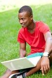 Studente africano sorridente dei giovani che si siede nell'erba con il taccuino Fotografia Stock Libera da Diritti