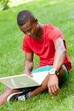 Studente africano sorridente dei giovani che si siede nell'erba con il taccuino Fotografie Stock Libere da Diritti