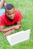 Studente africano sorridente dei giovani che si siede nell'erba con il taccuino Immagini Stock Libere da Diritti