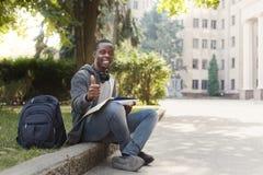 Studente afroamericano che si siede con il taccuino in campus universitario Fotografie Stock