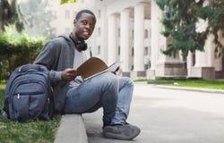 Studente afroamericano che si siede con il taccuino in campus universitario Fotografia Stock