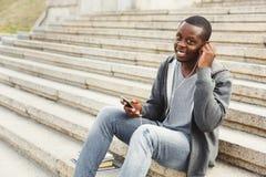 Studente afroamericano che si siede sulle scale e che ascolta la musica all'aperto Immagini Stock Libere da Diritti