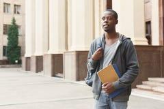 Studente afroamericano con i libri in campus universitario Immagine Stock