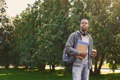 Studente afroamericano con i libri in parco all'aperto Fotografia Stock