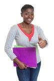 Studente afroamericano con lavoro di ufficio che mostra pollice Immagine Stock