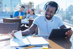 Studente afroamericano con le cuffie che studia all'aperto Fotografia Stock