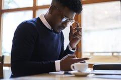 Studente afroamericano della scuola di commercio in maglione scuro e camicia bianca che inviano rapporto finanziario importante Immagine Stock