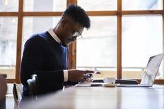 Studente afroamericano della scuola di commercio in maglione scuro e camicia bianca che si siedono nella caffetteria con il compu Fotografie Stock
