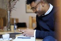 Studente afroamericano della scuola di commercio in maglione scuro e negli occhiali bianchi della camicia che scrive messaggio a  Fotografia Stock Libera da Diritti