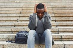 Studente afroamericano disperato che si siede sulle scale all'aperto Immagine Stock