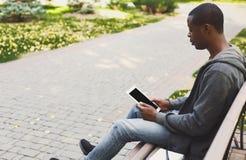 Studente afroamericano nel parco con i oudoors della compressa Fotografie Stock