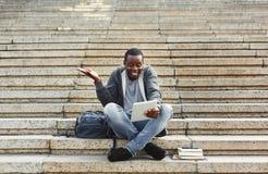 Studente afroamericano sorpreso che si siede sulle scale facendo uso della compressa digitale Immagini Stock