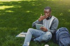 Studente afroamericano sorpreso su erba con i oudoors della compressa Immagini Stock Libere da Diritti