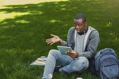 Studente afroamericano sorpreso su erba con i oudoors della compressa Immagine Stock