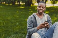 Studente afroamericano sorridente che ascolta la musica in parco all'aperto Immagine Stock