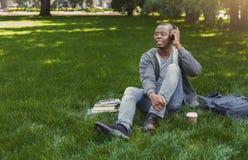 Studente afroamericano sorridente che ascolta la musica in parco all'aperto Immagini Stock