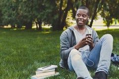 Studente afroamericano sorridente che ascolta la musica in parco all'aperto Fotografia Stock Libera da Diritti