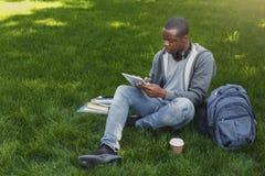 Studente afroamericano su erba con i oudoors della compressa Fotografia Stock