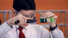 Studente alla scuola che fa un esperimento di scienza facendo uso dei reagenti, della provetta e del laser archivi video