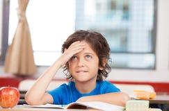 Studente alla scuola elementare che pensa alla soluzione dei problemi Fotografia Stock