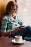 Studente allegro casuale che si siede accanto a mandare un sms della finestra Immagine Stock