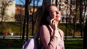 Studente allegro che cammina nel parco e che parla dallo smartphone r immagini stock