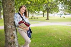Studente allegro che si appoggia albero che tiene i suoi libri Immagini Stock Libere da Diritti
