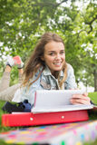 Studente allegro che si trova sull'erba che studia con il suo pc della compressa Fotografia Stock Libera da Diritti