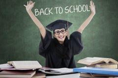 Studente allegro con l'abito di graduazione di nuovo alla scuola Immagine Stock Libera da Diritti