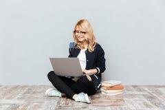 Studente allegro della giovane donna che per mezzo del computer portatile Fotografie Stock