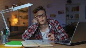 Studente annoiato che chiacchiera sul telefono con l'amico invece di studio, sprecante tempo stock footage