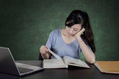 Studente annoiato che legge un libro nell'aula Immagini Stock Libere da Diritti