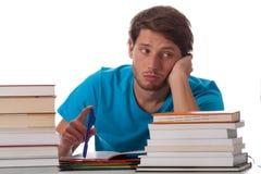 Studente annoiato che si siede nella biblioteca Fotografie Stock