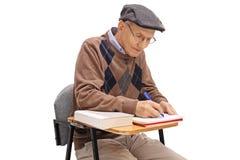 Studente anziano che si siede in una sedia della scuola e che prende le note Fotografia Stock