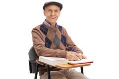 Studente anziano in una sedia della scuola che prende le note Fotografia Stock Libera da Diritti