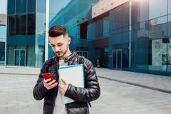 Studente arabo che per mezzo dello smartphone fuori Il tipo sicuro esamina il telefono davanti a costruzione moderna dopo le clas Immagine Stock