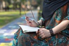 Studente arabo che si siede nel parco dell'università e che fa le note della mano Fotografia Stock Libera da Diritti