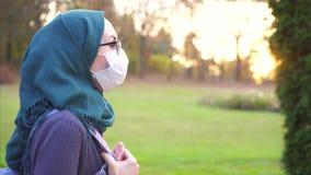 Studente arabo in vetri d'uso del hijab e fasciatura medica nel parco video d archivio