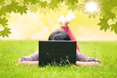 Studente asiatico che esamina computer portatile su erba verde Fotografia Stock