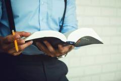 Studente asiatico che legge un libro della bibbia Fotografia Stock